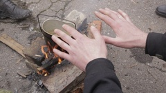 Bowler camp , cooking on a fire, man warming his hands over a fire Stock Footage