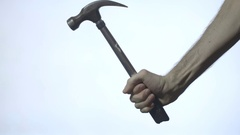 A hammer is gripped and swung in front of a white background Stock Footage
