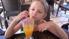 4K Child Drinking Orange Juice, Beach Restaurant, Local, Thirsty Girl at Terrace Stock Footage
