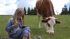 4K Child Playing Tablet, Smartphone Outdoor, Grazing Cow on Meadow in Mountains Stock Footage