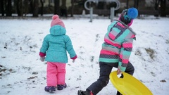 Two Little Sisters in Colorful Clothes Enjoying Snowy Weather and Sledge are Stock Footage
