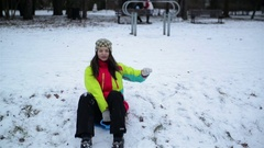 Woman with Charming Smile Wearing Warm Colorful Clothes is Sledding Down the Stock Footage