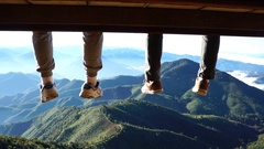 Two men legs hanging from the bench against a blue sky and mountains view. Stock Footage