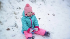 Toddler Girl Wearing Warm Snow Suit and Pink Knitted Hat is Sitting on Saucer Stock Footage