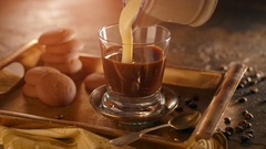 Coffee in a transparent glass. with pouring condensed milk on wooden table Stock Footage