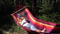 4K Child Playing Tablet in Hammock, Girl Relaxing in Forest, Wood, Outdoor View Stock Footage