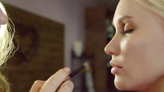 Young woman doing makeup on a model in a beauty salon. Stock Footage