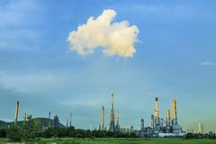 Green environment of heavy petrochemical industry plant against blue sky Stock Photos