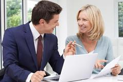Mature Woman Meeting With Financial Advisor At Home Stock Photos