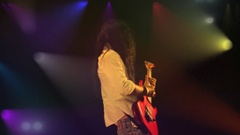 Powerful rock guitarist on big stage with a big light show plays hard his guitar Stock Footage