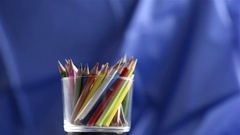 Closeup of colored pencils rotating over blue background. Seamless looping Stock Footage