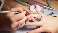 Manicurist paints woman's nails by brush, woman comes to the manicure salon Stock Footage