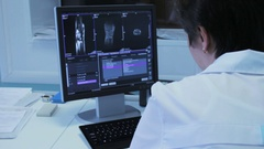 Female Doctor in Hospital looking at CT scan Stock Footage
