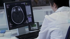 Doctor works at the computer with the imaging of the brain in real time Stock Footage