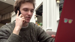 Young Man freelance outsource work Using Laptop In Cafe, Talking On Smartphone Stock Footage