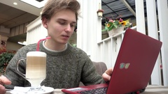 Young Man freelance outsource work Using Laptop In Cafe, drinking cocktail Stock Footage