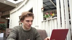 Young Man freelance outsource work Using Laptop In Cafe, using Smartphone Stock Footage
