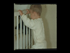 Portrait and cute little boy who learned how to climb into his crib Stock Footage