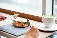 Woman eating salmon panini sandwich at restaurant Stock Photos