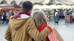 Lovely couple cuddling ath the christmas market in the town, steadycam shot Stock Footage