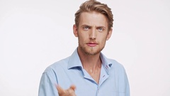 Young Caucasian male with brown beard and blue eyes standing on white background Stock Footage
