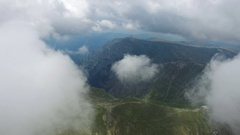 Bucegi mountains, Romania, aerial flight from the first layer of clouds Stock Footage