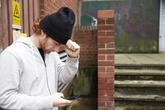 Waist up view of young man using phone in an urban setting Stock Photos