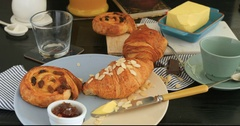 Filling glass of orange juice and a French breakfast with pastries and coffee Stock Footage