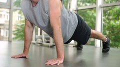 Man in sportswear doing push-up at gym Stock Footage