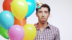 Happy Young Caucasian male with dark hair and light bristle wearing birthday cap Stock Footage