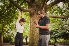 Personal trainer instructing woman on pull ups using park tree branch Stock Photos