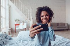 Pretty smiling african girl make selfie sitting on bed at home Stock Photos