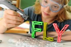 Boy with digital pen and 3D model of capital-lettered word in classroom Stock Photos