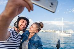 Young moped couple taking selfie on harbour, Split, Dalmatia, Croatia Stock Photos