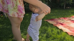 Young mother teaching making first steps her baby son on grass at backyard Stock Footage