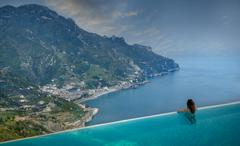 Rear view of woman looking out to coast from infinity pool, Ravello, Amalfi Stock Photos