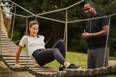 Personal trainer instructing woman training on playground equipment in park Stock Photos