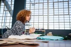 Mature female fashion designer leaning on workshop table looking at textiles Stock Photos
