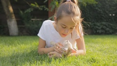 Portrait of beautiful girl caressing and hugging red cat on grass at garden Stock Footage