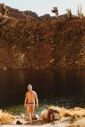 Male hiker in swimming trunks by lake drying face, Mineral King, Sequoia Stock Photos