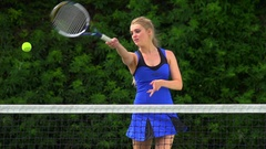 Pretty Young Tennis Player Volleys ball towards camera. Stock Footage