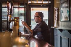 Barman reading smartphone texts at public house counter Stock Photos