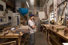 Guitar maker in workshop making telephone call on mobile phone Kuvituskuvat