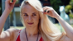 A young woman wearing a statement flower in hair on the beach Stock Footage