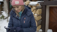 Young woman in winter ski resort using mobile phone, typing sms. Stock Footage