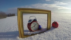 Golden art frame on field snow, Christmas bauble and clock, time lapse 4K Stock Footage
