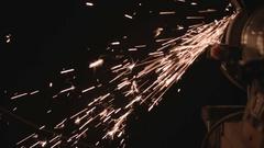 Dark shot of grinder in workshop spitting out sparks Stock Footage