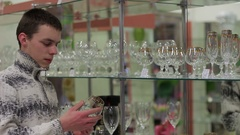 Young man chooses a crystal glass. Dishes shop Stock Footage