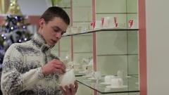 Man chooses kettle in utensils shop Stock Footage