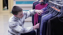 Man chooses pullover in a clothing store Stock Footage